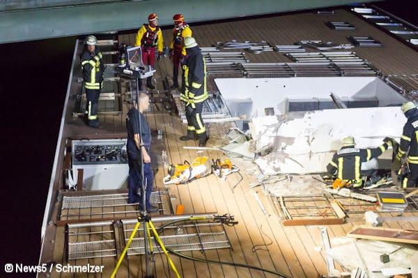Am fruehen Sonntagmorgen (11.09.2016) ging bei der Einsatzzentrale der Polizei gegen 1.35 Uhr ein Anruf ein, dass auf dem Main-Donau-Kanal ein Hotelschiff mit einer Bruecke kollidiert sein soll. Nachdem zunaechst unklar war, wo sich diese Stelle befindet, rueckten sowohl die Feuerwehr Nuernberg, wie auch die Feuerwehr Erlangen aus, um das havarierte Schiff so schnell wie moeglich zu finden. Nach kurzer Zeit war klar, dass sich die Stelle der Havarie in Erlangen, kurz vor der Schleuse Kriegenbrunn an der Bahnbruecke, ereignet hat. Den ersteintreffenden Kraeften bot sich ein erschreckendes Bild. Das Fuehrerhaus des Hotelschiffs, wohl besetzt mit 181 Passagieren und 79 Crewmitglieder, wurde bei der Kollision mit der Bruecke abgerissen. Fuer die Stadt Erlangen ist laut dem Einsatzleiter Feuerwehr Grossalarm fuer Feuerwehr und Rettungsdienst fuer das Stadtgebiet ausgerufen. Aktuell ist die Feuerwehr immer noch damit beschaeftigt das Schiff zu sichern, was bislang aber nicht gelungen ist, weil es immer wieder abtreibt und dadurch gefaehrliche Situationen fuer die Einsatzkraefte entstehen. Inzwischen wurde durch den Pressesprecher der Polizei, Michael Petzold, bestaetigt, dass zwei Menschen bei der Havarie getoetet wurden. Nach aktuellen Informationen von vor Ort soll sich wohl mindestens eine der Leichen noch im zerstoerten Fuehrerhaus befinden. Notfallseelsorger kuemmern sich um die Passagiere und Crewmitglieder, deren Rettung demnaechst anlaufen soll. Fuer die Rettungsmassnahmen wird von der Feuerwehr ein provisorischer Steg zum Schiff gebaut, ueber den Passagiere und Crew dann an Land gelangen sollen. Zum Bau des Stegs wurde nun das THW mit hinzugezogen, um eine groesstmoegliche Sicherheit fuer die Einsatzkraefte, die Passagiere und die Crew zu gewaehrleisten. Wie die Havarie zustande kam, ist bislang unklar. Das Hotelschiff war auf dem Main-Donau-Kanal Richtung Nuernberg unterwegs. Insgesamt sind 220 Einsatzkraefte von Feuerwehr, Wasserrettung, Rettungsdienst und THW