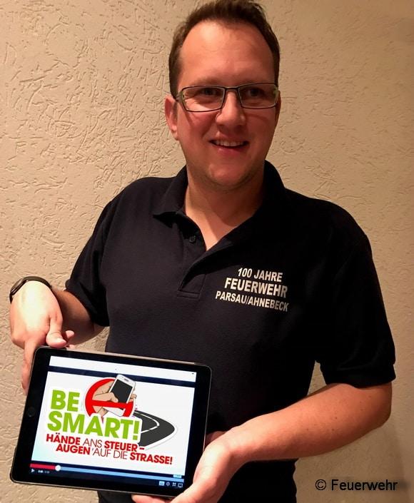 """Dennis Lenke, Pressewart der Feuerwehr parsau/Ahnebeck zeigt den Videoclip zur Kampagne """"Be Smart"""" auf einem Tablet. Foto: Feuerwehr"""