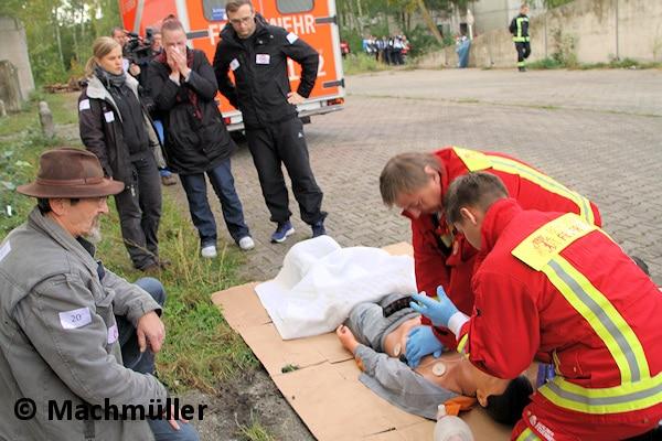 """Ausgangspunkt für die Übung war eine Reanimation. Nachdem zunächst Helfer den """"Patienten"""" - eine Übungspuppe - reanimiert hatten, übernahm der Rettungsdienst der Berliner Feuerwehr. Eine Angehörige wird im Hintergrund betreut. Foto: Machmüller"""