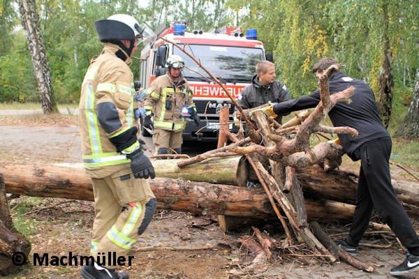 Freiwillige Helfer und Berliner Feuerwehrleute arbeiten Hand in Hand und räumen Baumstämme beiseite. Foto: Machmüller