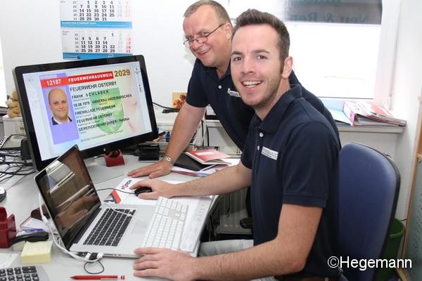 Michael Röder (links) hatte die Idee zu dem bundeseinheitlichen Feuerwehrausweis im Scheckkartenformat. Den Behördenverlag gründete dann Felix Rösler. Die Ausweise stellen die beiden Feuerwehrleute selbst her. Foto: Hegemann
