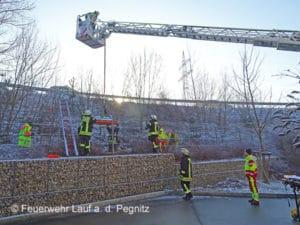 Per Drehleiter und Schleifkorbtrage rettet die Feuerwehr Lauf a. d. Pegnitz einen flüchtigen Fahrer, der verletzt hinter einem Zaun liegt. Foto: Feuerwehr Lauf a. d. Pegnitz