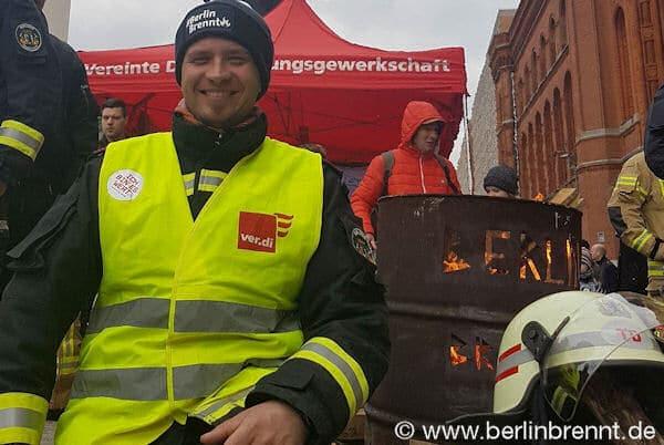 Der Verdi Betriebsgruppensprecher Stefan Ehricht neben der #BerlinBrennt Tonne