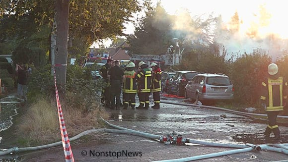 Feuerwehr auf Straße vor zerstörtem Haus