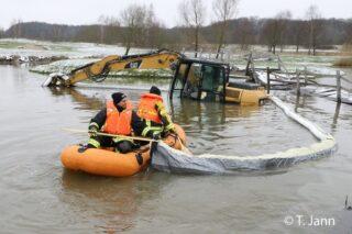 Feuerwehrleute legen mittels Schlauchboot eine Ölsperre um einen Bagger. Diesen hatten Unbekannte gestohlen und in einem See versenkt.