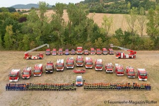 Die Feuerwehren von Bad Kissingen mit Feuerwehrfahrzeugen auf einer grünen Wiese