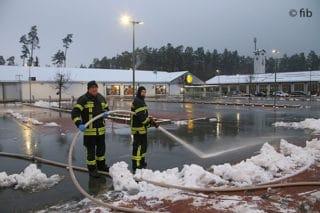 Feuerwehrleute mit Schlauch und Strahlrohr auf einem teilweise verschneiten Parkplatz