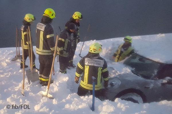 Feuerwehrleute im Schnee mit Pkw