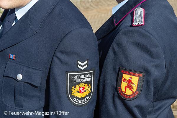 Zwei Feuerwehrleute aus Bremen und Niedersachsen stehen nebeneinander.
