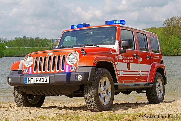 Ein Jeep der Feuerwehr Neckartailfingen steht am Strand eines Badeseesteht